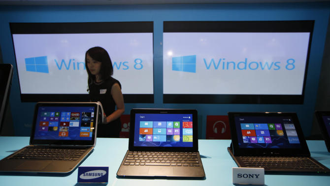 A woman walks past laptop computers running Microsoft Windows 8 operating system during its launching ceremony in Hong Kong Friday, Oct. 26, 2012. Microsoft launched a radical redesign of its world-dominating Windows operating system, introducing a touch-enabled interface that attempts to bridge the gap between personal computers and fast-growing mobile devices powered by the company's fiercest competitors. (AP Photo/Kin Cheung)