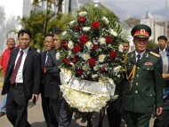 An official delegation from Vietnam arrives with a wreath in tribute to Venezuela's late President Hugo Chavez, as his body lies in state at the Military Academy in Caracas, March 7, 2013. REUTERS/Tomas Bravo