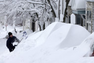 A man shovels snow off his car in front of his home on East Third street in the South Boston neighborhood in Boston, Saturday, Feb. 9, 2013. A howling storm across the Northeast left the New York-to-Boston corridor shrouded in 1 to 3 feet of snow Saturday, stranding motorists on highways overnight and piling up drifts so high that some homeowners couldn&#39;t get their doors open. More than 650,000 homes and businesses were left without electricity. (AP Photo/Gene J. Puskar)