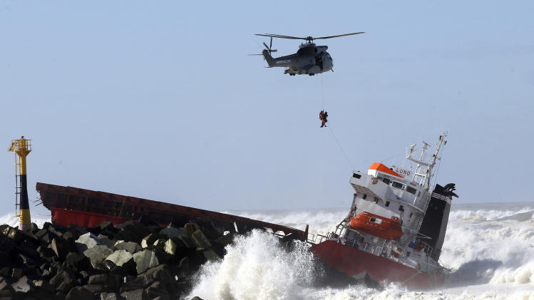 A sailor is lifted off by a military helicopter after a Spanish cargo ship that slammed into a jetty in choppy Atlantic Ocean waters off Anglet, southwestern France, Wednesday, Feb. 5, 2014. The hold of the ship, the Luno, was empty when the accident occurred along the coast of the town of Anglet, and a small amount of fuel was spilling into the water, officials said. The ship had been heading to a nearby port to load up with cargo when its engine conked out and the rough waves carried it into the jetty. (AP Photo/Bob Edme)