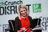 Marissa Mayer, President and CEO of Yahoo!, autographs a copy of Vogue magazine for moderator Michael Arrington of TechCrunch during a fireside chat session at TechCrunch Disrupt SF 2013 in San Francisco, California September 11, 2013. REUTERS/Stephen Lam/Files