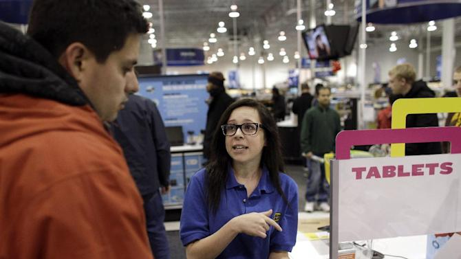 FILE - In this Friday Nov. 23, 2012, file photo, Best Buy electronics store employee Maddy Cooke, helps a customer looking at computers, in Broomfield, Colo.  Electronics chain Best Buy Co. said Tuesday, Feb. 26, 2013, it is cutting 400 jobs at its headquarters as part of a larger $725 million cost-cutting plan. (AP Photo/Brennan Linsley)