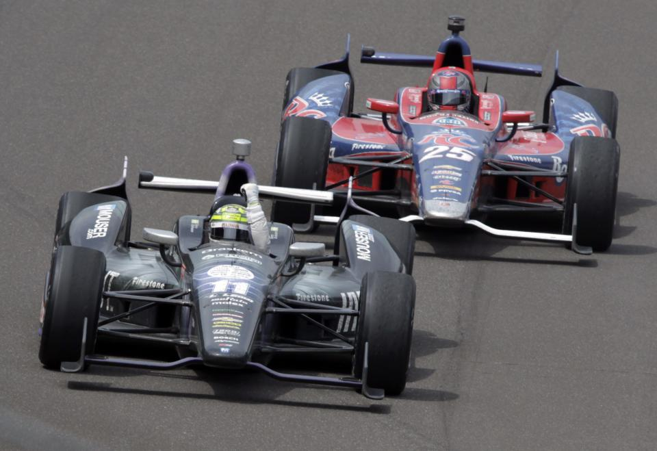 Tony Kanaan, of Brazil, pumps his fist in front of Marco Andretti to celebrate after winning the Indianapolis 500 auto race at Indianapolis Motor Speedway in Indianapolis, Sunday, May 26, 2013. (AP Photo/AJ Mast)