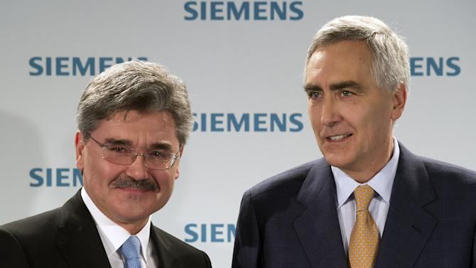 """CEO of  Siemens AG, Peter Loescher, right, and CFO Joe Kaeser attend a press conference in Munich, Germany, Monday Jan. 24, 2012.  Industrial equipment maker Siemens AG said Tuesday that net profit fell 17 percent to 1.46 billion euro ( US $ 1.89 billion) in the final quarter of 2011 due to delays in major wind-power and rail projects, and as the uncertain global economic outlook hurt orders.  Chief executive officer Peter Loescher said the result showed that troubles on financial markets from Europe's debt crisis """"have left their mark on the real economy"""" through weaker demand.  (AP Photo/dapd Joerg Koch)"""