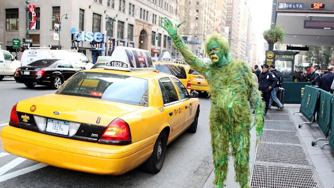 "In this Oct. 17, 2012 publicity image released by Madison Square Garden, Jeff McCarthy hails a cab dressed as The Grinch outside Madison Square Garden, where ""Dr. Seuss' How The Grinch Stole Christmas! The Musical"" is playing this Christmas season. (AP Photo/Madison Square Garden, Amanda Schwab/Starpix)"