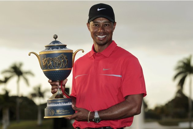 Woods poses with the Gene Sarazen Trophy after winning the 2013 WGC-Cadillac Championship PGA golf tournament in Doral