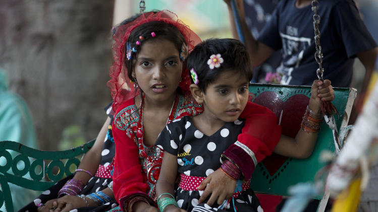 Pakistani children dressed up for the Eid al-Fitr holiday enjoy a ride at a park in Rawalpindi, Pakistan, Wednesday, July 30, 2014. The Eid al-Fitr Muslim holiday marks the end of the holy fasting month of Ramadan. (AP Photo/B.K. Bangash)