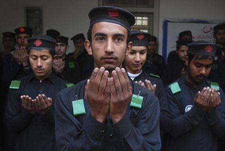 Students pray during assembly at a school after it reopened in Peshawar