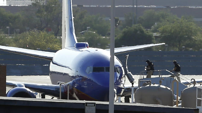 """Members of the bomb squad walk onto a Southwest Airlines plane on the ground at Phoenix Sky Harbor International Airport after the FBI says a """"telephonic bomb threat"""" against a Southwest flight from Los Angeles to Texas led to the plane being diverted to Phoenix on Monday, June 10, 2013. Flight 2675 left Los Angeles International Airport at 2:12 p.m. and was heading to Austin before the threat was received by telephone. The plane landed safely at the Phoenix airport at about 3 p.m. (AP Photo/Ross D. Franklin)"""