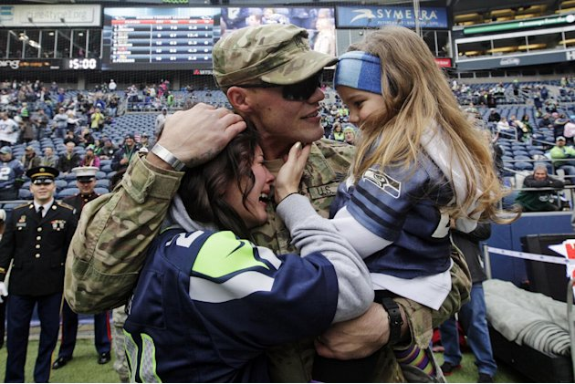 United States Army Sgt. Zach Ames, center, who has been on a one-year deployment to Afghanistan, surprises his wife, Bri Ames, left, and their daughter Emersyn, right, with a reunion prior to an NFL f