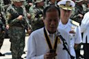 Benigno Aquino looks at his mobile phone after the navy's anniversary celebration at Fort San Felipe, on May 21, 2013