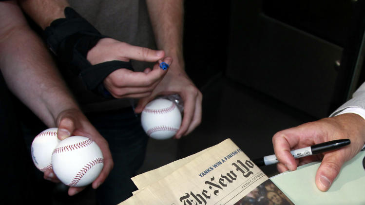 Autograph seekers wait for Former Major League Baseball pitcher RogerClemens to sign autographs after signing a newspaper , Thursday, May 17, 2012, in Washington, as his perjury trial concluded for the day. (AP Photo/Haraz N. Ghanbari)