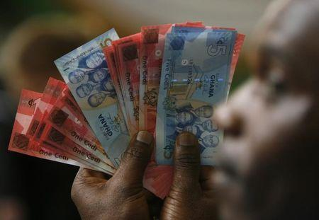A man holds Ghana's cedi notes in Accra
