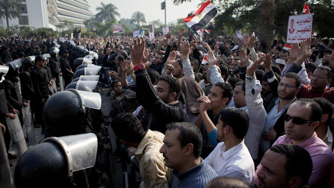 """Supporters of Egyptian President Mohammed Morsi chant slogans as riot police, left, stand guard in front of the entrance of Egypt's top court, in Cairo, Egypt, Sunday, Dec. 2, 2012. Egypt's top court announced on Sunday the suspension of its work indefinitely to protest """"psychological and physical pressures,"""" saying its judges could not enter its Nile-side building because of the Islamist president's supporters gathered outside. Arabic on the poster, right, reads, """"The people want to purify the states's institutions."""" (AP Photo/Nasser Nasser)"""