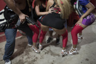 "In this Dec. 8, 2012 photo, a trafficker, left, holds a riffle as he dances with women at a funk ""baile"" in a slum in western Rio de Janeiro, Brazil. Huge funk ""bailes,"" or parties, go on past dawn, packed with shirtless young men who can be heavily armed drug dealers, in slums far from police control. Women wear barely there spandex getups and dramatize sexually explicit lyrics with hard-core, full-contact antics that would make an American stripper blush. (AP Photo/Felipe Dana)"