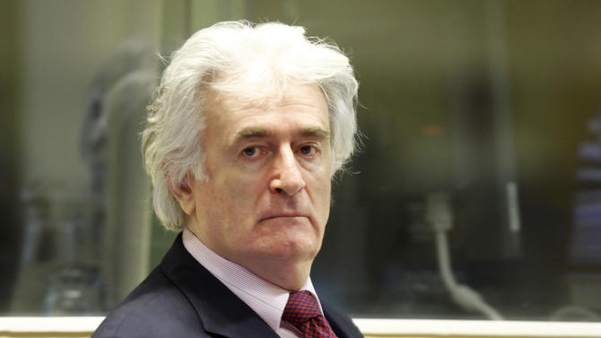 FILE - In this Nov. 3, 2009 file photo former Bosnian Serb leader Radovan Karadzic enters the courtroom of the U.N.'s Yugoslav war crimes tribunal in The Hague, Netherlands. Karadzic, 66, asked U.N. judges on Monday, June 11, 2012, to dismiss his war crimes case halfway through the trial. Prosecutors finished presenting evidence against Karadzic last month, and he is calling for dismissal of all or some charges before he presents his formal defense. (AP Photo/Michael Kooren/Pool, File)
