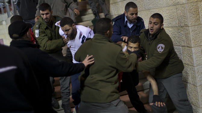Israeli security forces detain Bnei Sakhnin supporters during a game against Beitar Jerusalem F.C. at the Teddy Stadium in Jerusalem, Sunday, Feb. 10, 2013.  Hundreds of police deployed around Beitar Jerusalem's stadium, two days after a suspicious fire believed to be set by angry fans destroyed the team's main offices. Tensions remained high Sunday as the team faced off with Bnei Sakhnin, an Arab team whose fans have clashed before with Beitar's. (AP Photo/Bernat Armangue)