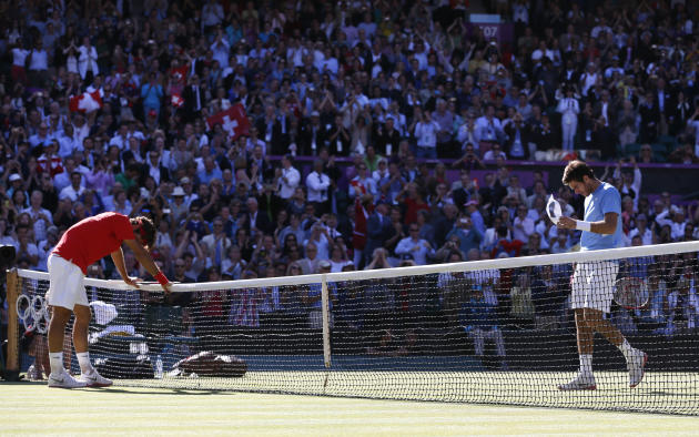 Switzerland's Federer rests on the net after winning his men's singles tennis semi-final match against Argentina's del Potro at the All England Lawn Tennis Club during the London 2012 Olympic Games