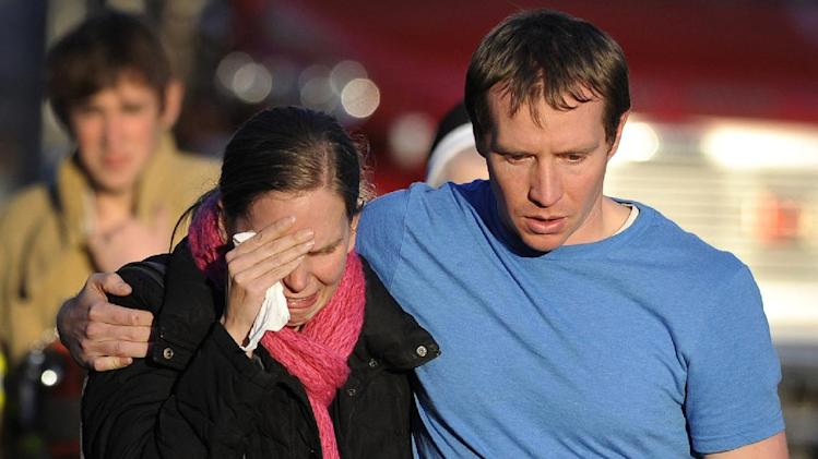 FILE--In this photo taken on Dec. 14, 2012, Alissa Parker grieves with her husband, Robbie, as they leave the firehouse staging area after receiving word that their daughter was one of the 20 children killed in the Sandy Hook School shooting in Newtown, Conn. The moment Alissa Parker learned of a shooting at her daughter's school, she suddenly regretted not pointing out what she had seen as security gaps at Sandy Hook Elementary School. Parker, whose 6-year-old daughter Emilie was among 20 first-graders killed in the Dec. 14 massacre, had thought security could have been tighter, although she never could have guessed it would be tested by a gunman with a military-style, semi-automatic rifle. (AP Photo/Jessica Hill, File)