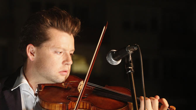Julian Rachlin, the first violinist with the Israel Philharmonic Orchestra, plays a Bach sarabande in front of the monument to the fighters of the Warsaw ghetto uprising in Warsaw, Poland, on Thursday April 18, 2013. The performance was part of an evening of commemorations on the eve of the 70th anniversary of the outbreak of the 1943 revolt. (AP Photo/Czarek Sokolowski)