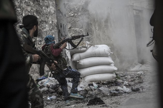 In this Wednesday, Oct. 24, 2012 photo, a rebel fighter retreats for cover as enemy fire targets the rebel position during clashes at the Moaskar front line, one of the battlefields in the Karmal Jabl
