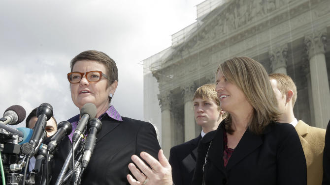 Plaintiffs Kris Perry, left, and her partner Sandy Stier, right, both from Berkeley, Cailf., meet with the media outside the Supreme Court in Washington, Tuesday, March 26, 2013, after the court heard arguments on California's voter approved ban on same-sex marriage, Proposition 8. (AP Photo/Pablo Martinez Monsivais)