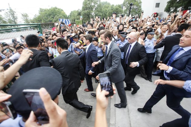 Fans push towards policemen as they take pictures and videos of former England soccer captain David Beckham upon his arrival at Tongji University, in Shanghai