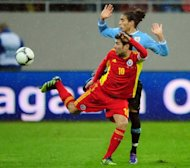 Adrian Mutu (foreground) clashes with Uruguay's Martin Caceres during a friendly between Romania and Uruguay in Bucharest in February. The former Chelsea and Juventus striker is on the verge of signing with French Ligue 1 outfit Ajaccio after club president Alain Orsoni revealed the two parties have agreed terms