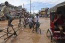 People move through a waterlogged street in Gauhati, India, Tuesday, July 16, 2013. Heavy showers flooded some areas in the city on Tuesday. (AP Photo/Anupam Nath)