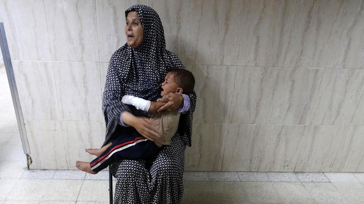 Palestinian woman holds her grandson, whom medics said was wounded in an Israeli air strike, at a hospital in Khan Younis in the southern Gaza Strip
