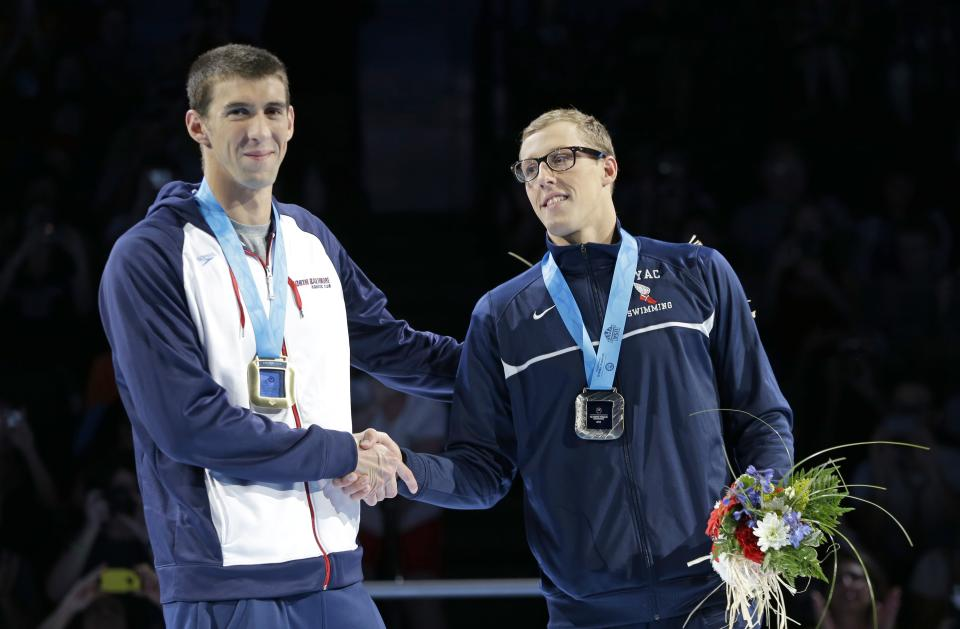 Michael Phelps, left, and Tyler McGill shake hands during the medal ceremony for the men's 100-meter butterfly at the U.S. Olympic swimming trials on Sunday, July 1, 2012, in Omaha, Neb. (AP Photo/Mark Humphrey)