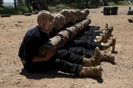Rebel fighters from 'the First Regiment', part of the Free Syrian Army, hold log as they participate in a military training in the western countryside of Aleppo