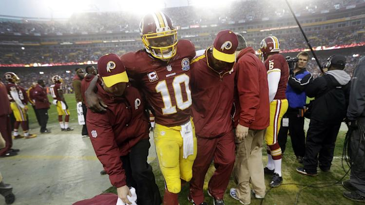 Washington Redskins quarterback Robert Griffin III is helped off the field after an injury during the second half of an NFL football game against the Baltimore Ravens in Landover, Md., Sunday, Dec. 9, 2012. Griffin suffered a sprained knee at the end of a 13-yard scramble. The Redskins won 31-28. (AP Photo/Patrick Semansky)
