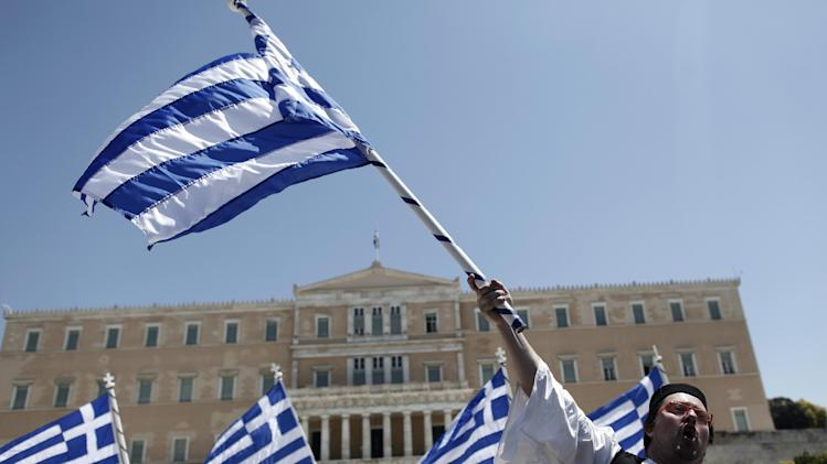 A municipal workers dressed in traditional  costume waves a Greek flag outside Greece's Parliament during a protest against government plans to lay off thousands of public sector workers as part of its austerity program, in Athens, on Friday, April 26, 2013. Under the terms of international bailouts that have kept it afloat since 2010, Greece has pledged to sack 15,000 civil servants over the coming two years. (AP Photo/Petros Giannakouris)