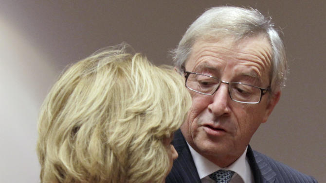 Luxembourg's Prime Minister Jean-Claude Juncker, right, puts his arm around Spain's Finance Minister Elena Salgado during a round table meeting of the eurogroup at the EU Council building in Brussels on Tuesday, Nov. 29, 2011. The 17 finance ministers of countries that use the euro converged on EU headquarters Tuesday in a desperate bid to save their currency and to protect Europe, the United States, Asia and the rest of the global economy from a debt-induced financial tsunami. (AP Photo/Virginia Mayo)