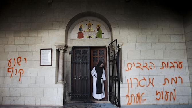 """FILE- In this Sept. 4, 2012, file photo, a Catholic monk stands in a doorway of the Latrun Trappist Monastery where Israeli police say vandals spray-painted anti-Christian and pro-settler graffiti and set the monastery's door on fire, in Latrun, between Jerusalem and Tel Aviv, Israel. After a series of attacks on Christian holy sites in Israel, Roman Catholic church officials recently issued a rare """"declaration"""" calling on Israeli leaders to take action against vandalism and violence.(AP Photo/Oded Balilty, File)"""