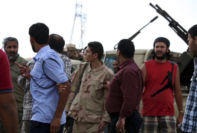 Members of the Rafallah Sahati Islamic Militia Brigades, argue with a Libyan policemen, second left, regarding a request for the militia to evacuate their base in Benghazi, Libya, Saturday, Sept. 22, 2012. On Friday evening hundreds of protesters angry over last week's killing of the U.S. ambassador to Libya stormed the compound of the Islamic extremist Ansar al-Shariah Brigade militia suspected in the attack, evicting militiamen and setting fire to their building Friday. After taking over the Ansar compound, protesters then drove to attack the Benghazi headquarters of Rafallah Sahati where militiamen opened fire on the protesters, who were largely unarmed, leaving at least 20 wounded and several killed according to hospital sources. (AP Photo/Mohammad Hannon)