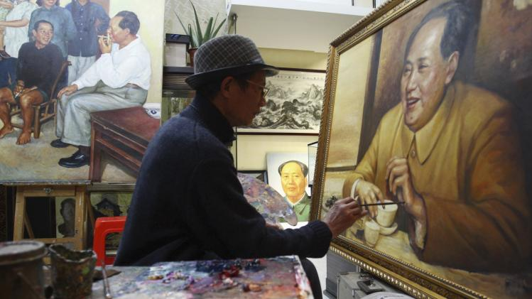 Yang Keqi improves his painting, a portrait of China's late chairman Mao Zedong, in Changsha