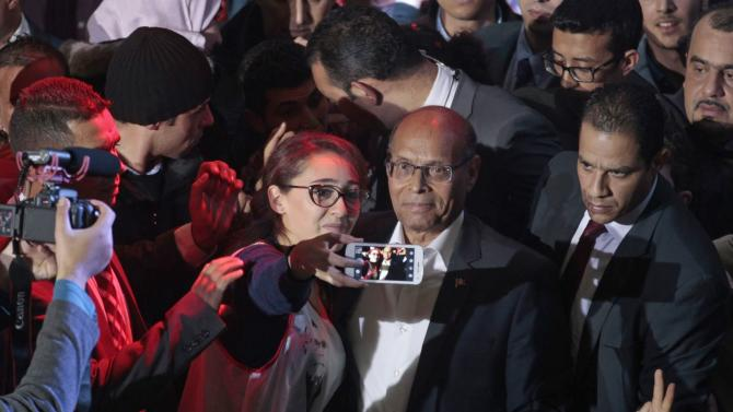 Tunisia's President Moncef Marzouki takes pictures with supporters during a re-election campaign in Tunis
