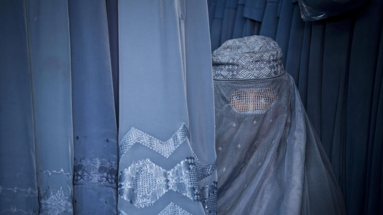 In this Thursday, April 11, 2013 photo, an Afghan woman peers through the  the eye slit of her burqa as she waits to try on a new burqa in shop in the old town of Kabul, Afghanistan. Despite advances in women's rights, Afghanistan remains a deeply conservative country and most women continue to wear the Burqa. But tradesmen say times are changing in Kabul at least, with demand for burqas declining as young women going to school and taking office jobs refuse to wear the cumbersome garments. (AP Photo/Anja Niedringhaus)