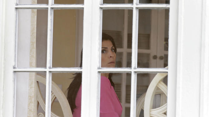 Jill Kelley looks out the window of her home Tuesday, Nov 13, 2012 in Tampa, Fla. Kelley is identified as the woman who allegedly received harassing emails from Gen. David Petraeus' paramour, Paula Broadwell. She serves as an unpaid social liaison to MacDill Air Force Base in Tampa, where the military's Central Command and Special Operations Command are located. (AP Photo/Chris O'Meara)