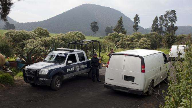 Vans belonging to Mexican authorities arrive at the entrance of a ranch where a mass grave was found in Tlalmanalco, Mexico, Thursday, Aug. 22, 2013. Mexican authorities said Thursday that they have found a mass grave east of Mexico City and are testing to determine if it holds some of the 12 people who vanished from a bar in an upscale area of the capital nearly three months ago. (AP Photo/Ivan Pierre Aguirre)