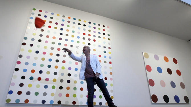 British artist Damien Hirst throws his cap while posing for photographers in front of  1-Methylcutosine, left, and Minocidil during the press preview of Damien Hirst: The Complete Spot Paintings 1986 – 2011 at Gagosian Gallery, Wednesday, Jan. 11, 2012 in Chelsea neighborhood of New York. Hirst's color spot paintings are being shown simultaneously at the Gagosian gallery's 11 locations around the world. The exhibition opens Thursday and runs through Feb. 10. (AP Photo/Mary Altaffer)
