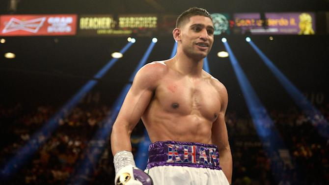 Amir Khan smiles as he heads to his corner while taking on Luis Collazo during their welterweight bout at the MGM Grand Garden Arena on May 3, 2014 in Las Vegas, Nevada