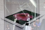 Pedestrians walk past an Apple store advertising the iPad. Apple has paid $60 million to end a dispute over who could use the iPad name in China, a court said Monday, giving the US tech giant more certainty in selling its tablet computer in the Chinese market