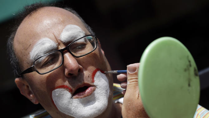 """Kenny the Clown,"" otherwise known as Kenneth Kahn, applies make-up as he readies to perform in San Francisco, Friday, Aug. 17, 2012. Kahn says he unwittingly received a stolen iPad from a friend who was later arrested for breaking into former Apple CEO Steve Jobs' residence in Palo Alto. Kahn said he had the stolen iPad for a few days before police came asking for the purloined tablet, which was returned to the Jobs family. The professional entertainer said he never examined the device's contents. Instead he downloaded the ""Pink Panther"" and other songs to play while entertaining kids and tourists during his clown routine. Kahn said had no idea where the 64GB iPad came from until his friend, 35-year-old Kariem McFarlin of Alameda, Calif., was arrested Aug. 2. (AP Photo/Marcio Jose Sanchez)"