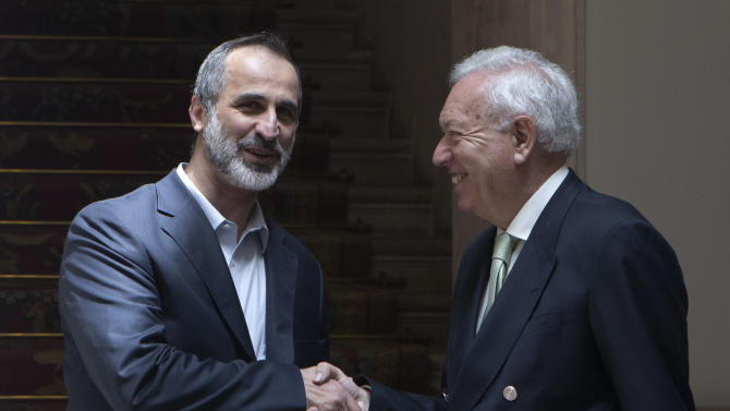 Mouaz al-Khatib, former chief of the Syrian National Coalition, left, shakes hands with Spain's Foreign Minister Jose Manuel Garcia-Margallo on his arrival at the foreign ministry in Madrid, Spain Tuesday May 21, 2013. Syrian opposition groups meeting in Spain say they oppose all negotiation with President Bashar Assad's government unless it is aimed at his giving up of power. Some 80 opposition representatives from inside and outside the country concluded a two-day meeting Tuesday, saying Assad would neither form part of any transition government nor have any role in Syria's future. (AP Photo/Paul White)