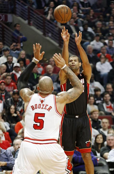 Miami Heat forward Shane Battier, right, shoots over Chicago Bulls forward Carlos Boozer, left, during the first half of an NBA basketball game in Chicago, Thursday, Dec. 5, 2013