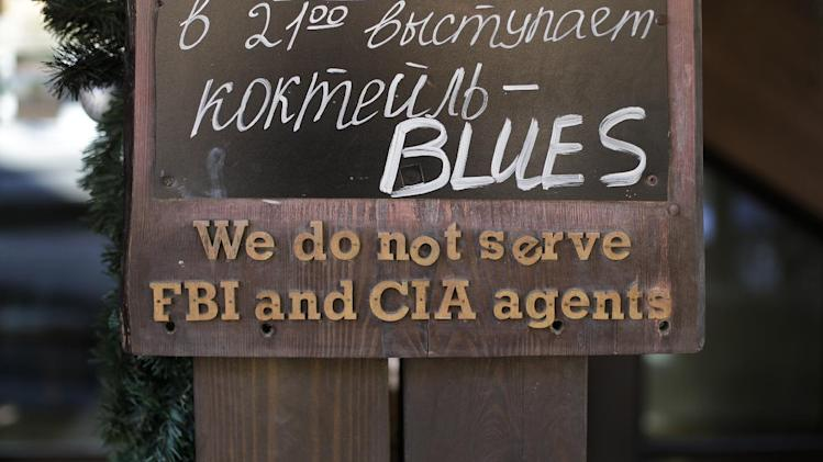 "A sign that says ""We do not serve FBI and CIA agents,"" hangs outside a restaurant on the opening day of the 2014 Winter Olympics, Friday, Feb. 7, 2014, in Krasnaya Polyana, Russia"