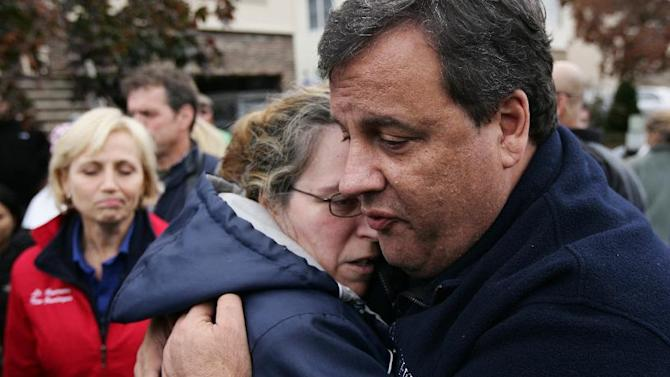 New Jersey Gov. Chris Christie tries to comfort Alice Cimillo and other Moonachie, N.J. residents whose homes were damaged by Superstorm Sandy, Thursday, Nov. 1, 2012, during a tour of the flood-ravaged area. The flooding of Moonachie, Little Ferry and Carlstadt, three communities sandwiched between Teterboro Airport, MetLife Stadium and the Hackensack River, was caused by six dirt berms that broke from the pressure of a tidal surge, Christie said. More than 1.7 million customers in New Jersey remain without power _ down from over 2.7 million at the height of the outages. (AP Photo/The Record of Bergen County, Kevin R. Wexler, Pool)